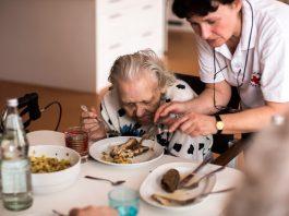 Eine Altenpflegerin hilft einer Bewohnerin beim Essen.
